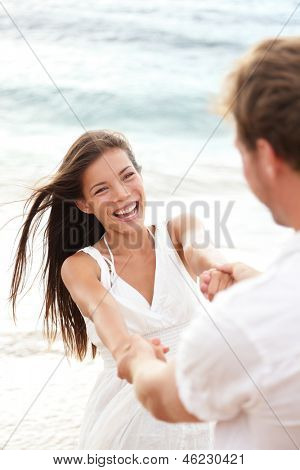 Beach summer vacation fun with playful young couple playing together enjoying their date or honeymoon laughing happy and elated. Multiracial couple, mixed race Asian woman and Caucasian man.