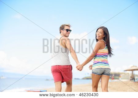 Beach vacation fun with cool trendy hipster couple. Two people running playful holding hands on summer travel holidays. Multi-ethnic interracial young couple, Asian woman, Caucasian man at ocean sea.