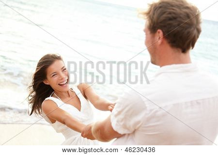 Happy young couple having beach fun on vacation travel holidays. Asian woman and man playing playful enjoying love on date or honeymoon. Multiracial couple in their 20s.