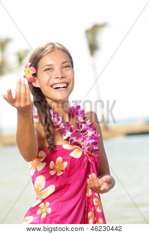 Hula dancer woman dancing hula dance on Hawaii wearing Hawaiian orchid flower lei smiling happy on beach. Travel vacation summer holidays image of beautiful mixed race girl in colorful pink sarong.