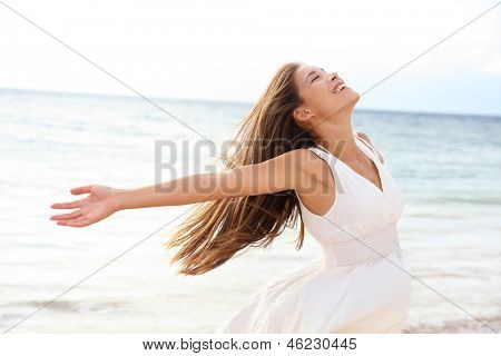 Woman relaxing at beach enjoying summer freedom with open arms and hair in the wind by the water seaside. Mixed race Asian Caucasian girl on summer travel holidays vacation outside.