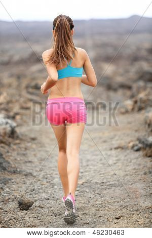 Trail runner woman running cross-country run training outside for marathon. Jogging female athlete working as part of healthy lifestyle. Rear view showing back from behind of woman runner on Hawaii.