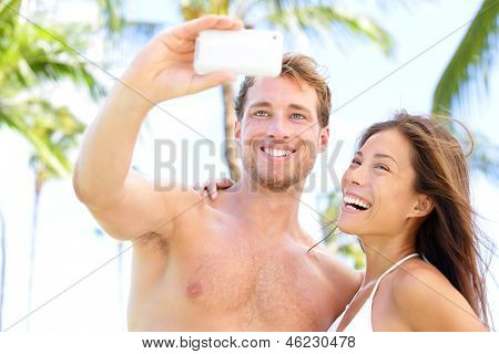 Vacation couple on beach taking pictures with camera phone. Romantic couple photographing self-portrait having fun on summer holidays travel on tropical beach. Interracial couple, Asian woman.