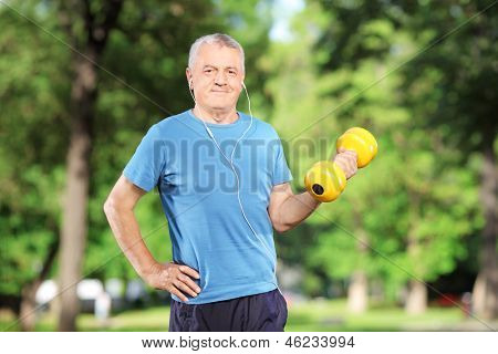 Mature man exercising with weight in a park