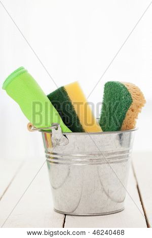 Cleaning sponges in a silver pail on a white wooden table