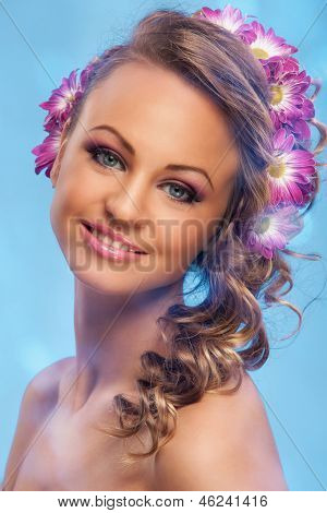 Beautiful young caucasian woman with flowers in her hair over blue background