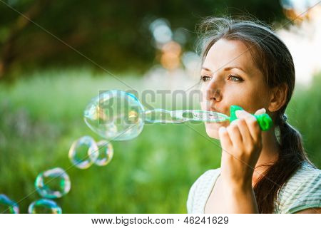 Girl Blowing Soap Bubbles In The Park