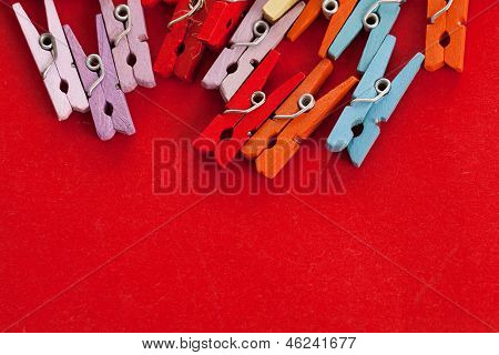 Closeup image of little colorful office clothespins on a red background