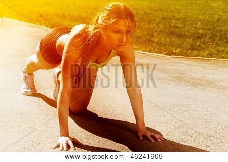 Beautiful young woman getting ready to run from lying pose