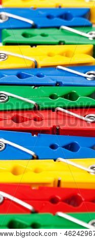 Closeup image of colorful clothespins on a white background