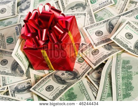 Red gift box on heap of $100 dollar bills