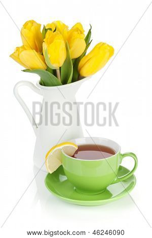 Yellow tulips and tea cup with lemon slice. Isolated on white background