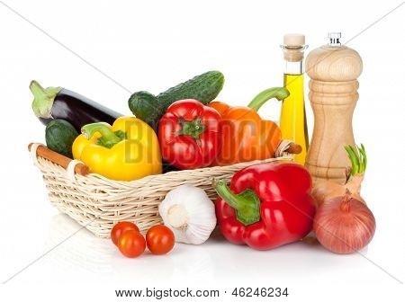 Fresh ripe vegetables in basket with pepper shaker and olive oil. Isolated on white background