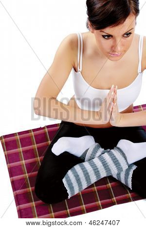 A young sportive girl sitting on the floor, isolated on white, from above