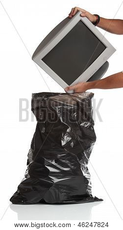 Man throwing a pc monitor in the garbage bag