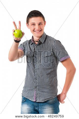 Young man with green apple showing victory sign isolated on white background