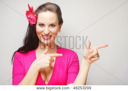 Portrait of friendly young woman pointing up, smiling at camera.