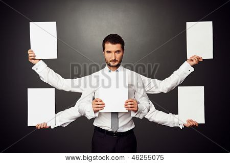 earnest man holding five white empty placards over dark background