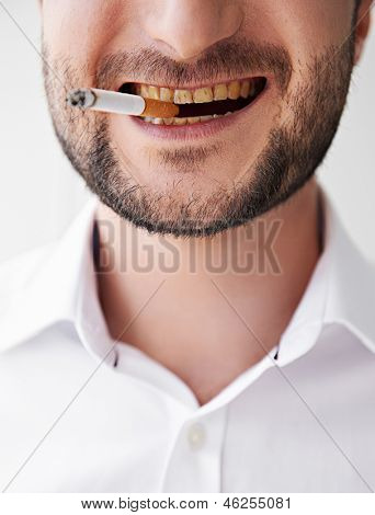 close-up photo of smoking man with dirty yellow teeth