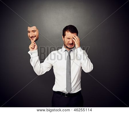 crying man holding mask with smiley face