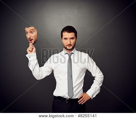 serious businessman holding mask with amazed face