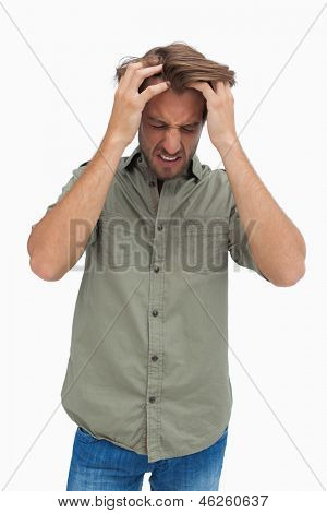 Frustrated man pulling his hair and looking down on white background