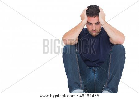 Sad man sitting on the floor while holding his head on white background