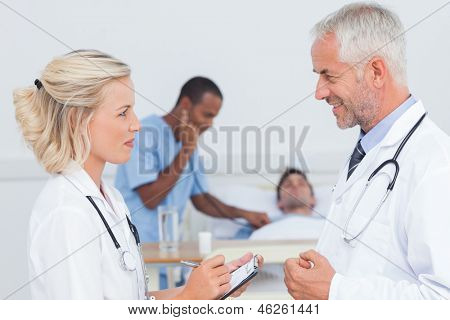 Smiling doctors speaking together in front of the patient