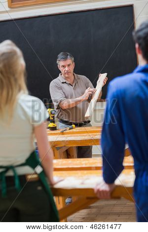 Teacher holding a wooden board while explaining something to his class