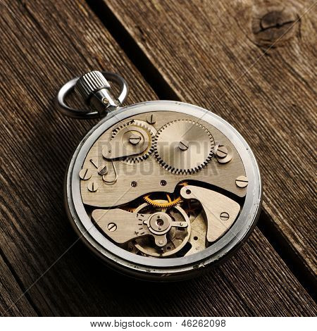 Clockwork mechanism over wooden background