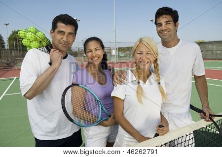 Portrait of four mixed doubles tennis players at net on tennis court