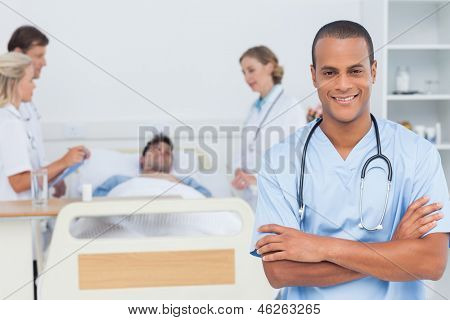 Attractive doctor with arms crossed standing in front of medical team taking care of a patient