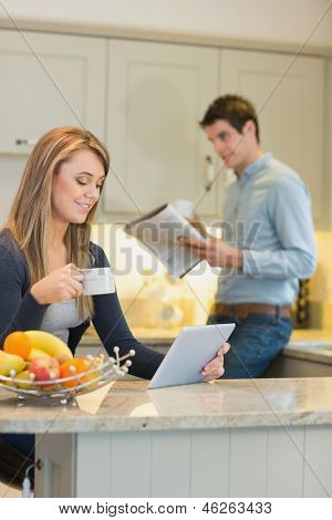 Woman with beverage and tablet computer and man with newspaper in kitchen