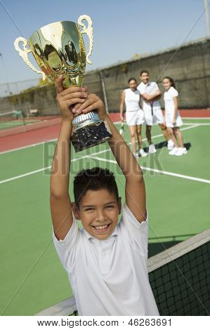 Portrait of a boy holding Tennis up trophy at net with adults in the background on tennis court