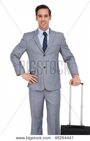 Smiling young businessman waiting with his luggage on white background