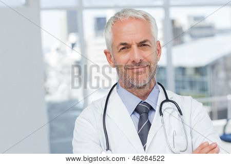 Serious doctor with arms crossed looking at the camera