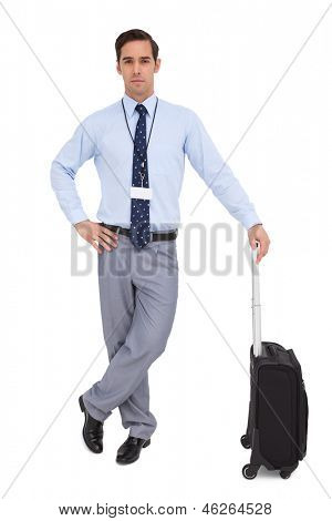 Handsome young businessman waiting with his suitcase on white background