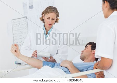Doctor taking the blood pressure of male patient in hospital