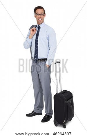 Smiling businessman standing next to his luggage on white background