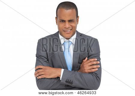 Doubtful young businessman with arms crossed on white background