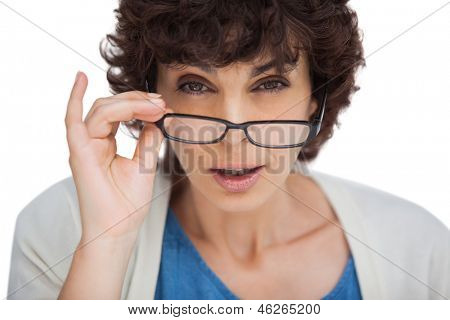 Portrait of a shocked woman looking over her glasses on white background