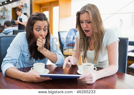 Women holding a tablet and looking surprised while sitting in canteen