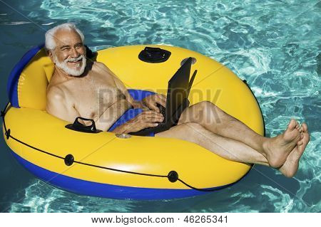 Porträt des leitenden glücklich liegend auf aufblasbare Floß mit Laptop im Schwimmbad