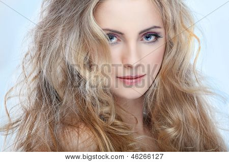 Closeup portrait of sexy whiteheaded young woman with beautiful blue eyes on blue  background
