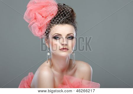 portrait of beautiful girl with a hat from a pink veil