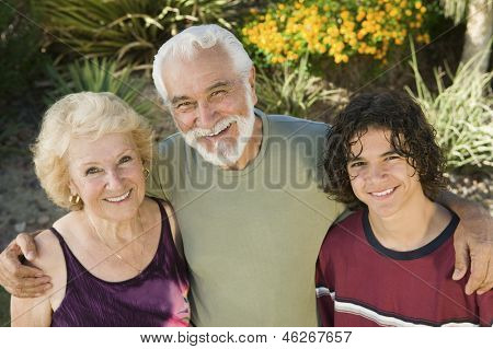 Teenage boy (13-15) with grandparents outdoors elevated view portrait.