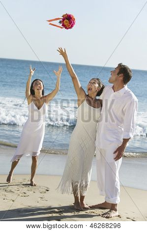 Newlywed couple with happy bride throwing her bouquet towards the bridesmaid on beach