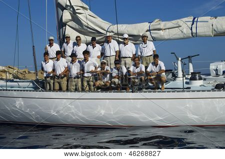 Sailing crew posing for a group portrait on board against clear blue sky