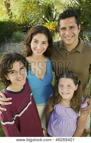 Girl (7-9) with brother (13-15) and parents outdoors elevated view portrait.