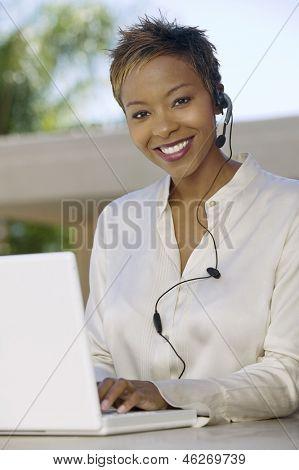 Portret van een glimlachende jonge ondersteuning telefoon operator in hoofdtelefoon met laptop in het patio